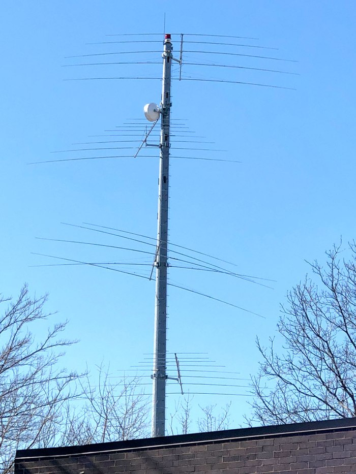 Una foto de una torre celular con múltiples niveles de antenas que sobresalen de ella.